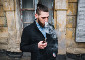 Guy with  beard smoking electronic cigarette outdoor